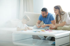 Spending time at home. Young parents and their son drawing with highlighters at home royalty free stock photos