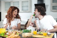 Carefree girl having fun with her parents in kitchen stock photos