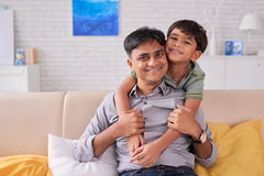 Spending time with son. Joyful father and his smiling kid on sofa at home Stock Images