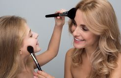 Cheerful woman and small girl are applying some powder stock photography