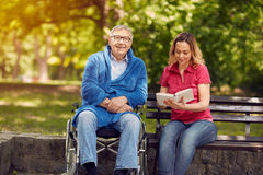 Spending time together reading book outdoor daughter and smiling. Spending time together reading book outdoor cheerful daughter and smiling disabled father in stock photos