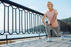 Spenslig äldre kvinna som gör utfall på bron Royaltyfri Bild