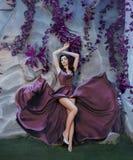 Spenslig attraktiv dam som bilden av den ursnygga konstnären som flyger fladdra den purpurfärgade långa satängklänningen som måla royaltyfria bilder