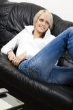 Spenslig blond kvinna i jeans som hemma kopplar av arkivbild