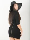 Spenslig härlig asiatisk flicka i liten svart klänning och en svart bredbrättad hatt royaltyfri foto