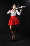 Spenslig kvinna som spelar fiolen på en svart bakgrund Royaltyfri Bild