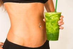 Spenslig kvinnlig torso garvad tonad kropp blandad fruktSmoothie Arkivfoton