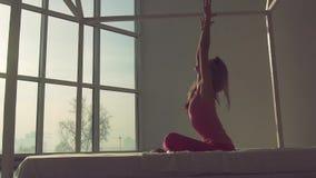 Spenslig passformkvinna som hemma gör yoga med naturligt ljus arkivfilmer
