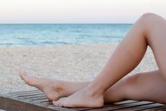 Spensliga ben av en flicka på en deckchair av trä, på stranden royaltyfri fotografi