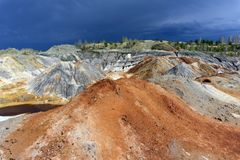 Spent clay quarry with multi-colored slopes. Landscape of spent clay quarry with eroded multi-colored slopes Royalty Free Stock Image