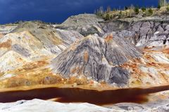 Spent clay quarry with multi-colored slopes. Landscape of spent quarry for clay mining with eroded multi-colored slopes Stock Image
