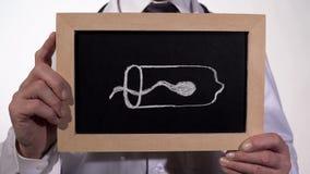 Spermatozoïde à l'intérieur du préservatif dessiné sur le tableau noir dans des mains de docteur, contraception photos libres de droits