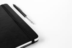 Sperren Sie einen Notizblock ein, der auf einem weißen Segeltuchhintergrund mit dem selektiven Konzentrieren auf Stift lokalisier Stockbilder