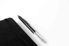 Sperren Sie einen Notizblock ein, der auf einem weißen Segeltuchhintergrund mit dem selektiven Konzentrieren auf Stift lokalisier Lizenzfreies Stockbild