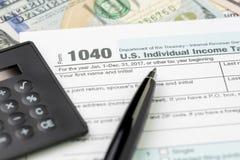 Sperren Sie 1040 füllende Form der US-Individualeinkommensteuer mit schwarzer Taschenrechner- und Dollar-Rechnung, Steuerunterord lizenzfreie stockbilder