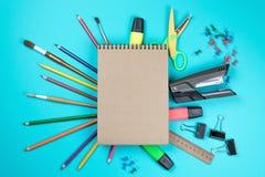 Sperrt bunte schreibende Werkzeugzusätze des Briefpapiers Bleistifte, das Kraftpapier ein, das auf blauem Hintergrund lokalisiert stockfotos