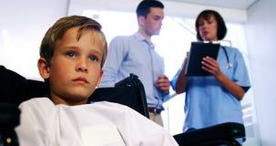 Sperrungsjunge, der auf Rollstuhl am Krankenhaus sitzt stock video