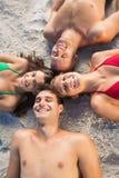 Spese generali degli amici sorridenti che si trovano insieme in un cerchio Fotografia Stock Libera da Diritti
