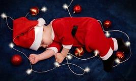 Spese generali del bambino che dormono in attrezzatura di Santa con le luci leggiadramente Fotografia Stock Libera da Diritti