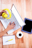 Spese generali delle mani femminili che scrivono sul computer portatile e che tengono le cuffie Fotografie Stock