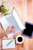 Spese generali delle mani femminili che scrivono sul computer portatile e che tengono le cuffie Fotografia Stock