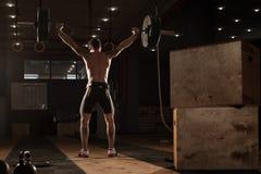 Spese generali di sollevamento del bilanciere del giovane uomo muscolare Immagini Stock