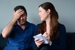 Spese preoccupate dell'elenco della moglie e del marito fotografie stock libere da diritti