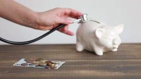 Spese sanitarie concetto, soldi sullo scrittorio e porcellino salvadanaio con stetoscope stock footage