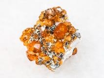 spessartine在白色的石榴石石头未加工的水晶  图库摄影