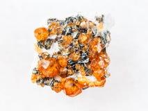 spessartine石榴石粗砺的水晶在白色的 库存照片