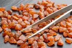 Spessartit garnets. Pile of brightly orange, uncut spessartite or spessartine garnets with tweezers on black stone plate stock images