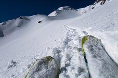 Spetsar av att turnera skidar efter spår in mot bergpasserande Arkivfoto