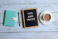 Spetsar och trick som är skriftliga på en svart tavla arkivfoto