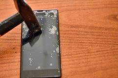 Spetsen av hammaren slogg sk?rmen av smartphonen royaltyfria foton