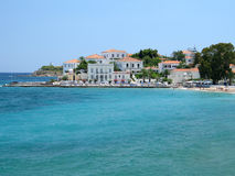 Spetses Town. A part of Spetses island town, Greece; traditional houses, a small beach, and a lighthouse can be seen royalty free stock photo