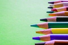 Spetsiga färgrika blyertspennor för Closeup på grön bakgrund arkivfoton