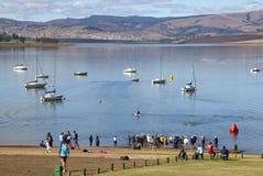 Spettatori ai nuotatori incoraggianti di triathlon del bordo delle acque Immagini Stock
