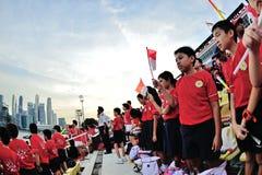 Spettatori che cantano l'inno nazionale di Singapore durante la ripetizione 2013 di parata di festa nazionale (NDP) Fotografie Stock Libere da Diritti