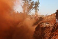 Spettatori che guardano automobile rossa calciare la nuvola di polvere rossa massiccia Fotografie Stock Libere da Diritti