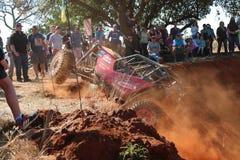Spettatori che guardano la fucilazione rossa dell'automobile con la ruota anteriore sospesa Immagine Stock Libera da Diritti
