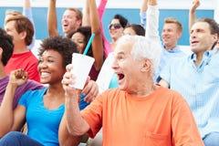 Spettatori che incoraggiano all'evento di sport all'aperto Fotografia Stock
