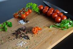 Spezia del coltello di rucola di molti pomodori Fotografia Stock