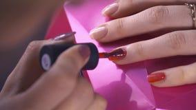 Spezialist bedeckt den Nagel des Kunden durch roten Lack Abschluss oben stock video footage