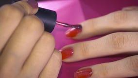 Spezialist bedeckt den Nagel des Kunden durch roten Lack Abschluss oben stock footage
