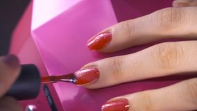 Spezialist bedeckt den Nagel des Kunden durch roten Lack Abschluss oben stock video