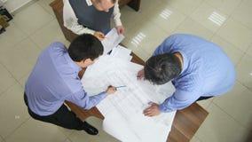 Spezialisten besprechen und betrachten das neue Projekt, das auf Blättern dargestellt wird stock video