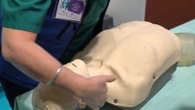 Spezialistenarzt demonstriert die modernen Mannequins für Fähigkeiten der ersten Hilfe Ausstellung der medizinischer Ausrüstung u stock video footage