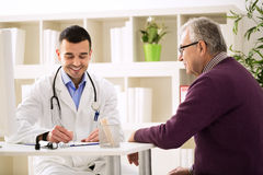 Spezialistendoktor und -patient lächeln und sprechen Lizenzfreies Stockfoto