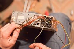 Spezialistenreparatur der alte Autoradio cassetter Recorder auf Knie Stockfotos