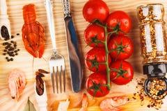 Spezie, argenteria fra i pomodori ciliegia e cancri immagini stock